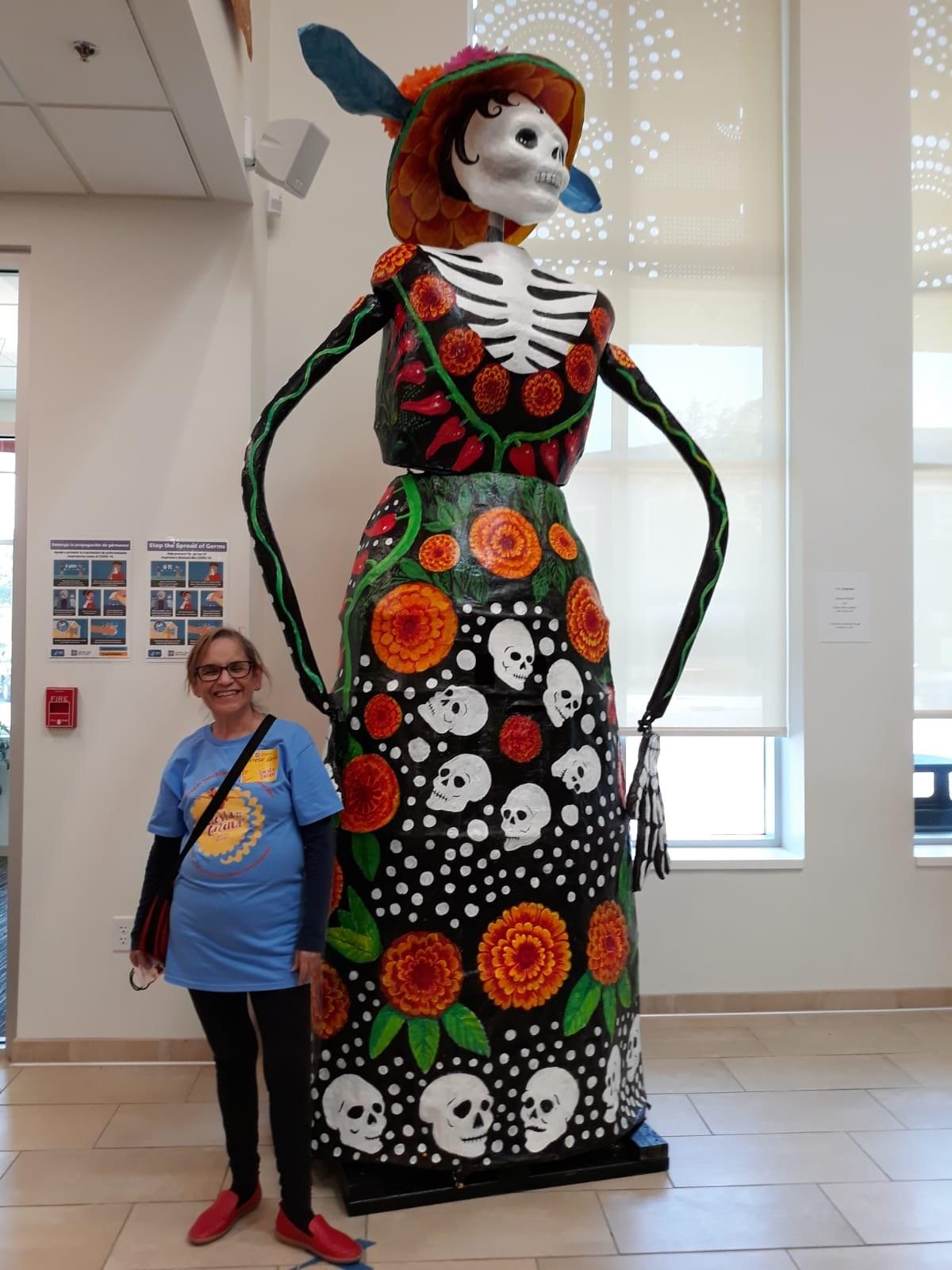 A woman standing next to a 13 foot tall calavera puppet.