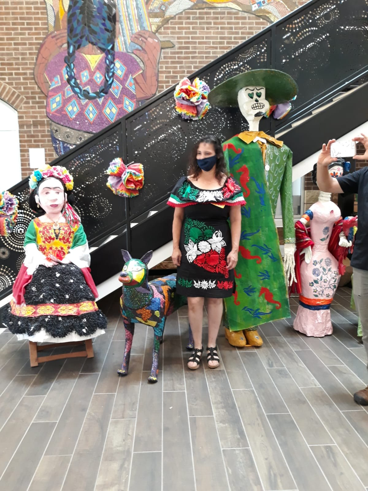 A woman standing next to several calavera puppets.
