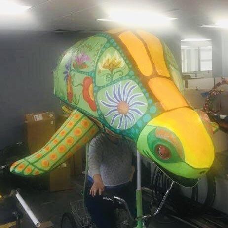 A huge turtle bike puppet.