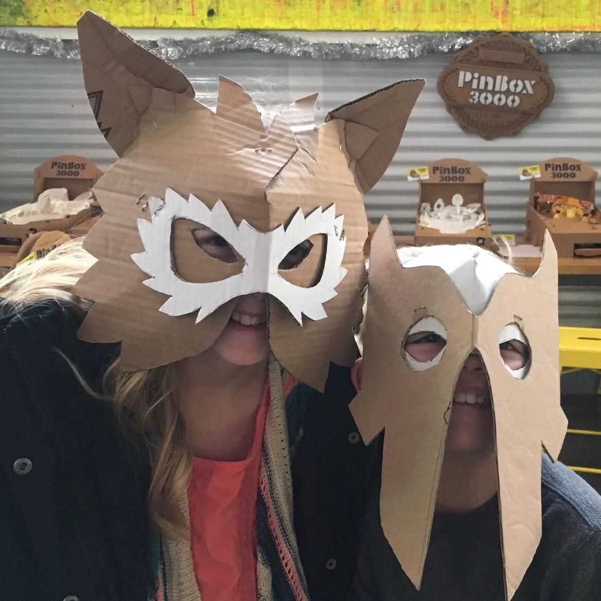 People wearing fancy cardboard masks.