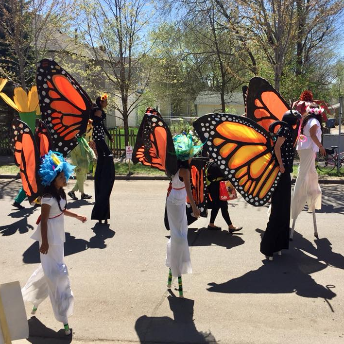 Stilters wearing monarch wings at the May Day parade.